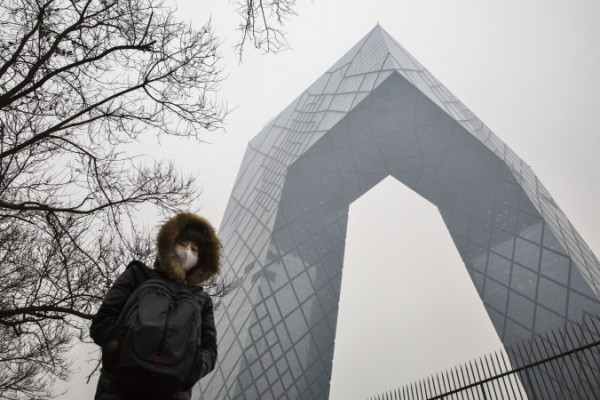 8 Aralık 2015'de Çinli bir bayan, CCTV binasını yanından geçerken hava kirliliğine karşı kendini korumak için bir maske takıyor. (Kevin Frayer/Getty Images)