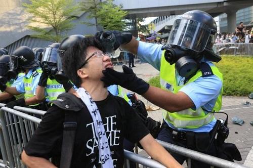Bir polis bir protestocunun gözlerine püskürttüğü biber gazını kendi elleriyle temizlerken (Fotoğraf: Yu Gang, Epoch Times)