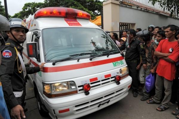 23 Kasım 2010 tarihinde Phnom Penh hastanesinden bir ambulans çıkarken bir polis ona eşlik ediyor. Bu hastane, yapılan baskın sonucu Kamboçya'daki organ ticareti zincirinde bir halka olarak adlandırılmaya başlandı. (Tang Chhin Sothy/AFP/Getty Images)